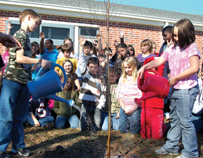 Joel Harrell (left) and Tabitha Chandler water the tree.