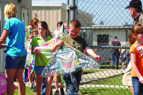 First grader Zachary Gainey eyes his shark kite. Also pictured in the background is Savannah Smallwood.