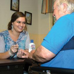 Keltni Davis gives resident Alvin Melton a manicure.