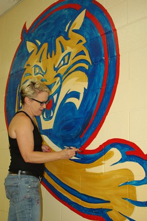 BCHS art teacher Tiffany Armoreda paints the new lunch room mural at BCMS.