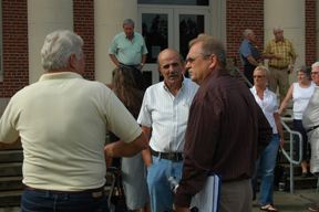 Commissioner Jimmy Anderson (right) speaks with resident Danny Burger (center) and others outside the courthouse the evening of August 20.