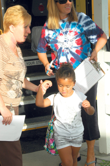 Tammy Brownlee helps pre-K student Breanna Fuller off the bus on the first day of school.