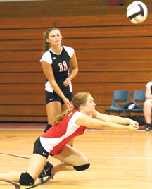 Kayla Holland looks on as Reagan McKendree volleys the serve.