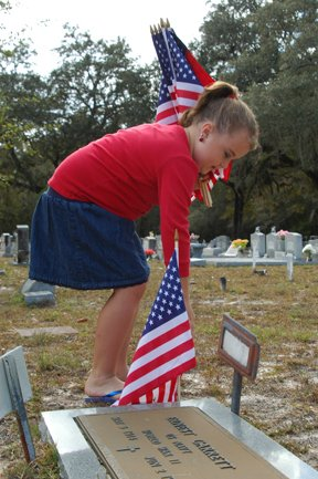 Josie Jacobs, 8, plants a flag at a veteran's grave at Macedonia Cemetery on Veterans Day.