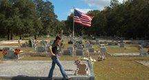 Rachel Harrison scouts the cemetery for unflagged veterans graves.