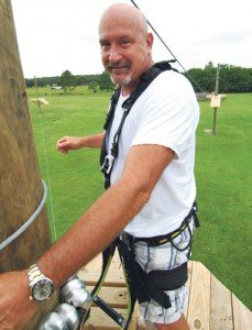 Mr. Broughton atop a scaled down version of his proposed zip line park located at his home off Mud Lake Road.