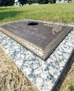 A gaping hole is left in grave marker above, perhaps due to the theft of a metal flower vase.