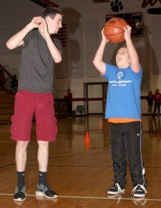 Senior Tyler Curry instructs Adam Varnadore, 15, in a shooting drill.