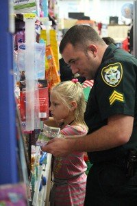 Deputy Drew Norman helps a child select toys.